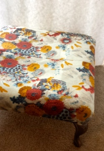This is a footstool I bought for $5 and I'm going to change the fabric…I kinda like the colors, but it's old and gross.